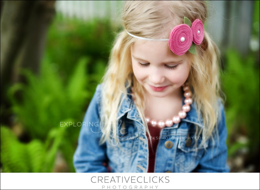 beautiful little girl in garden of ferns