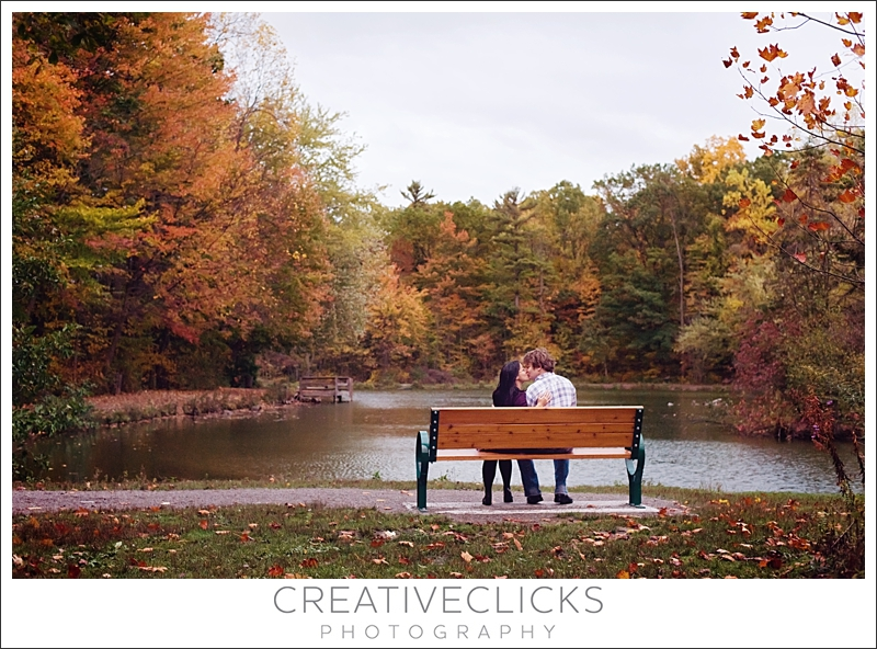 Couple Sitting on Bench Overlooking Lake