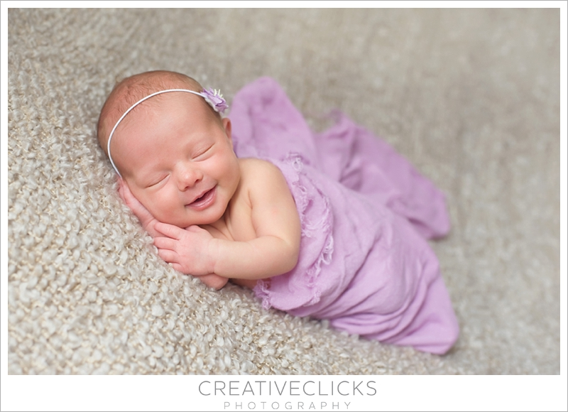 Smiling baby wrapped in purple