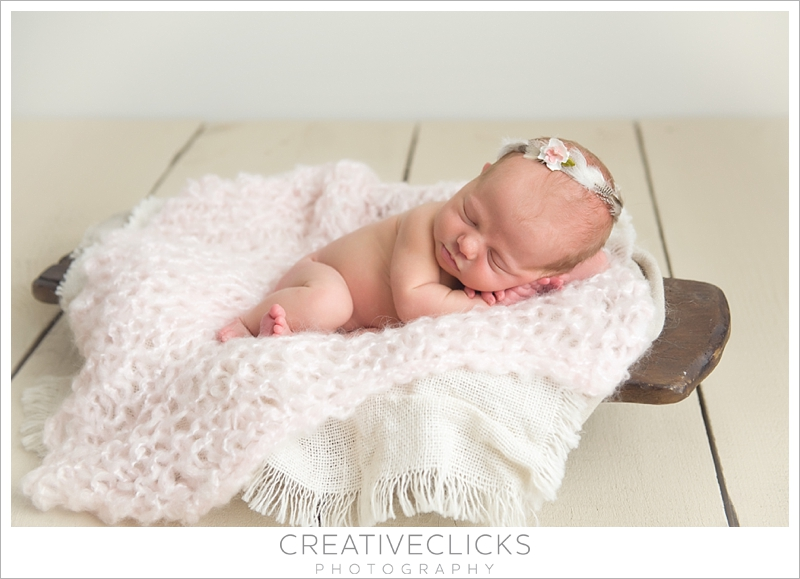 Newborn baby girl sleeping in trech bowl wearing feather crown