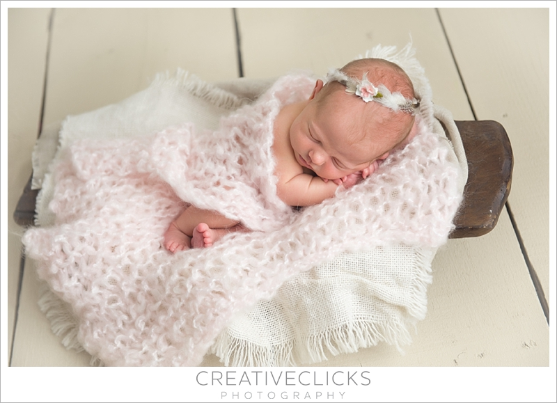Newborn Baby wrapped in pink in trenchbowl wearing feather crown