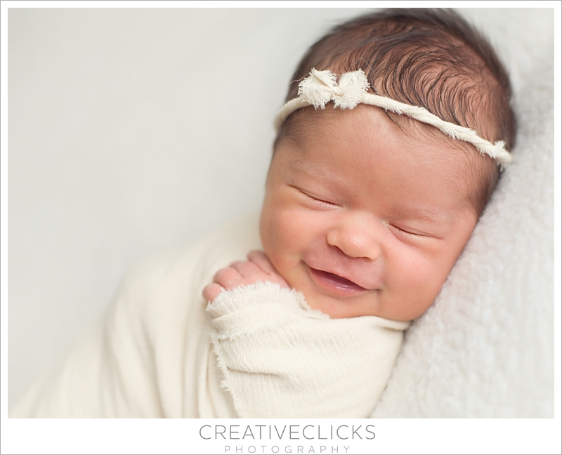 Smiling baby girl wrapped in cream wearing bow tieback