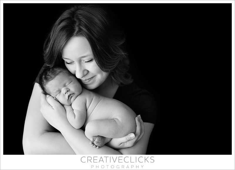 Smiling mother looks down at her newborn baby girl black and white portrait