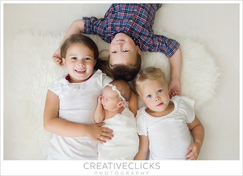 Newborn baby girl with her three older siblings lying on their backs