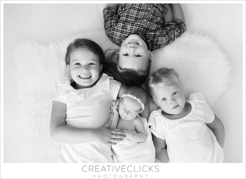 Newborn baby photographed with her three older siblings