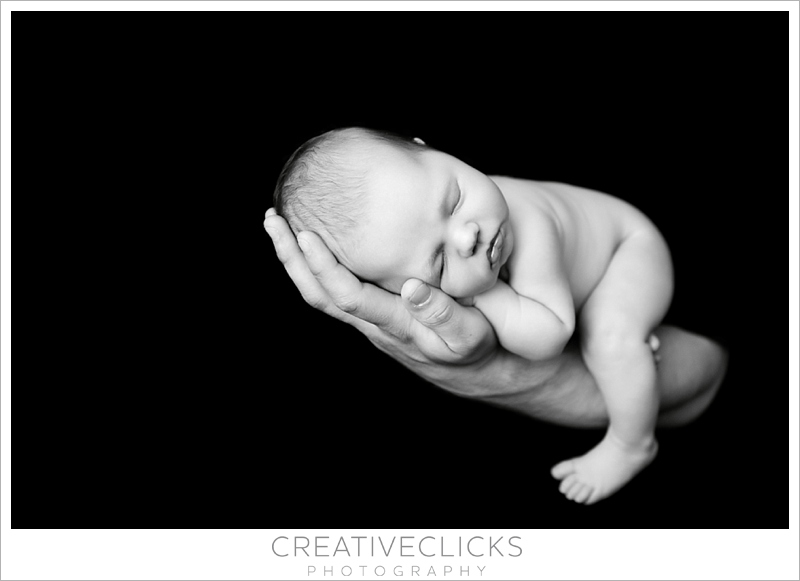 Newborn baby girl sleeping on Dad's outstretched arm Balck and white photograph