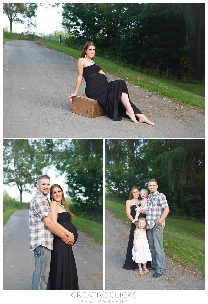 Expectant mother in long black dress posing with husband and daughters