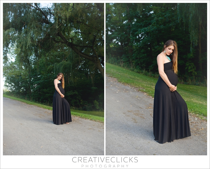 Pregnant mother posing in long black dress in front of willow tree