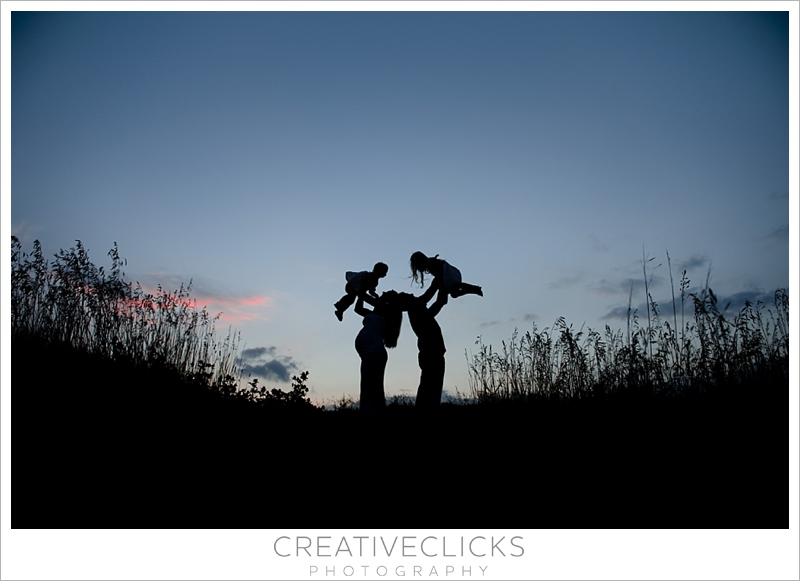 Sunset silhouette of family together on hill maternity session