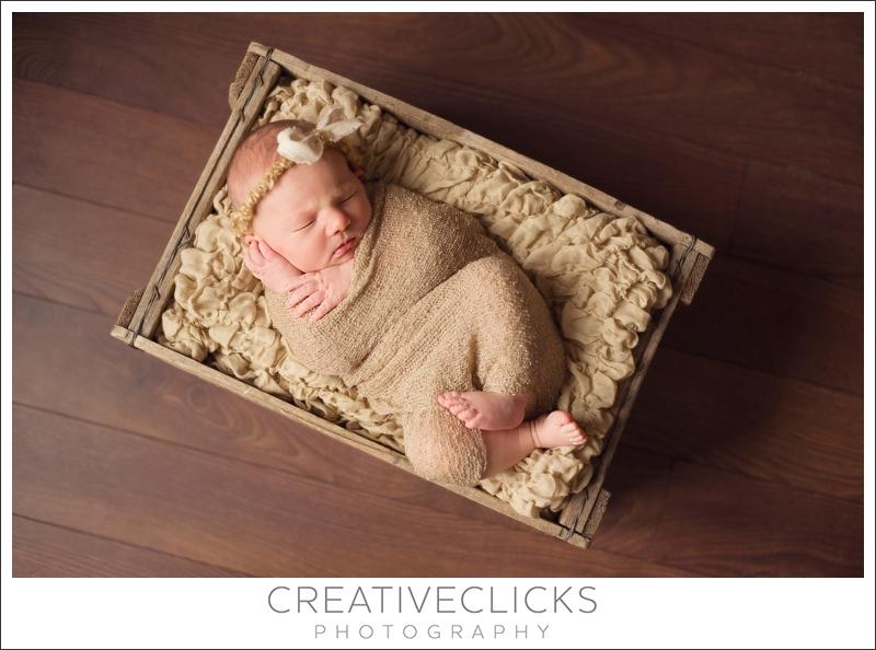 Sweet newborn baby sleeping in wooden crate