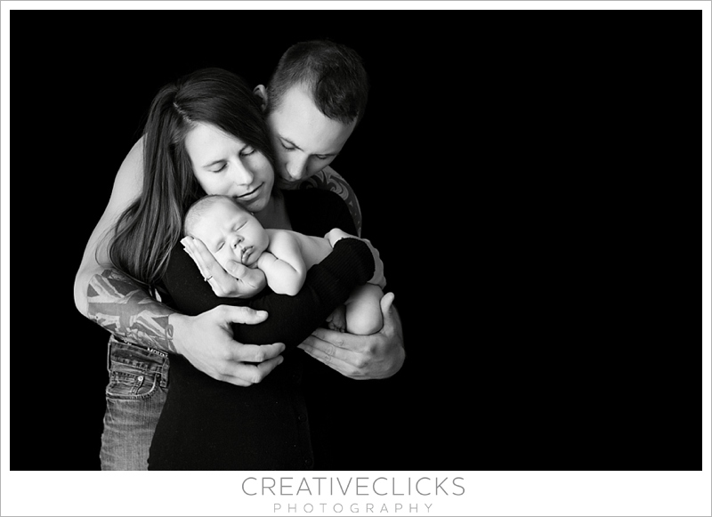 Newborn in moms arms wrapped in dads arms newborn family portrait black and white